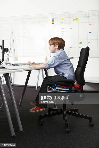 Boy sitting on ring binders on office chair using computer