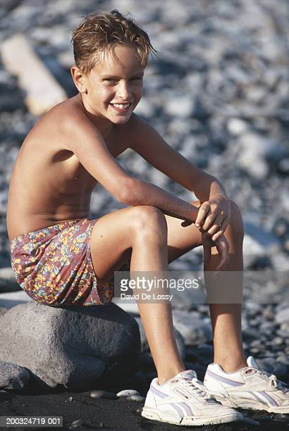 Boy (8-9) sitting on rock at pebbled beach, smiling