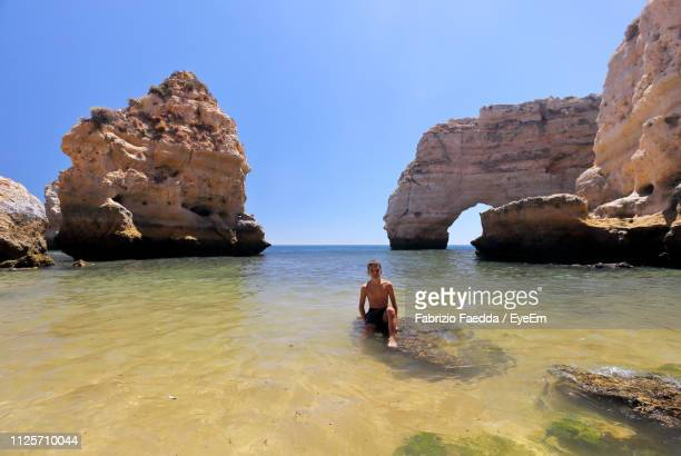 boy sitting on rock at sea against sky - cape verde stock pictures, royalty-free photos & images