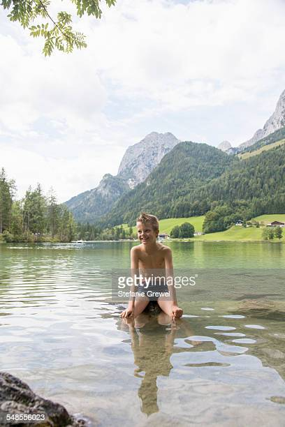 boy sitting on rock in lake, hintersee, zauberwald, bavaria, germany - zwembroek stockfoto's en -beelden