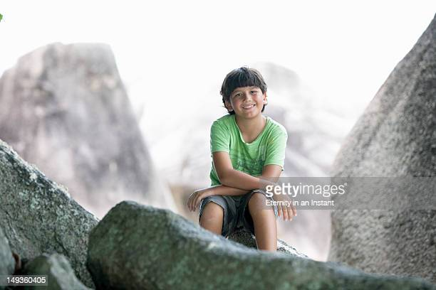 Boy sitting on rock, portrait
