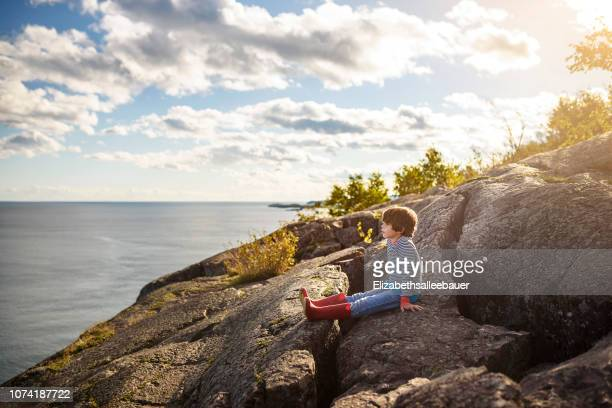 boy sitting on rocks by a lake, lake superior provincial park, united states - lake superior provincial park stock pictures, royalty-free photos & images