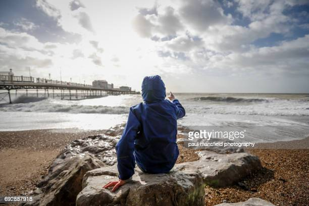 Boy sitting on rocks on Worthing seafront