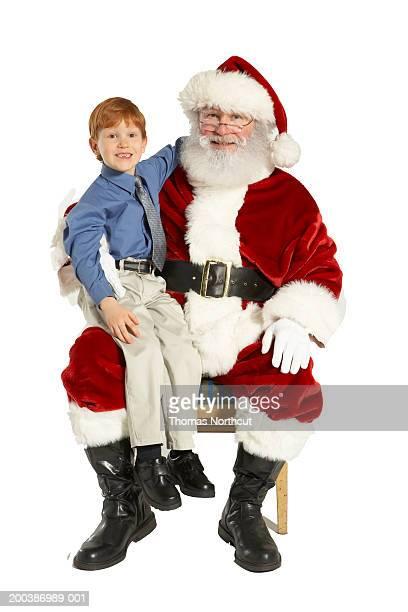 Boy (4-6) sitting on Santa's lap, smiling, portrait
