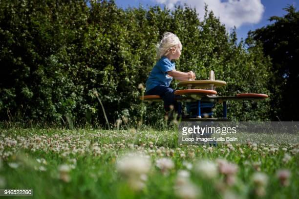 Boy sitting on see saw
