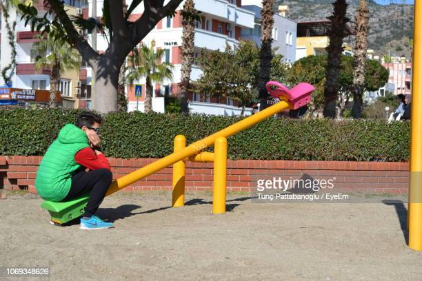 boy sitting on seesaw at park during sunny day - seesaw stock pictures, royalty-free photos & images