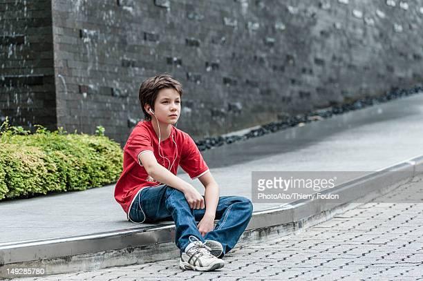 Boy sitting on sidewalk listening to music with earphones