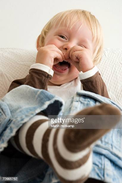 Boy sitting on sofa and laughing