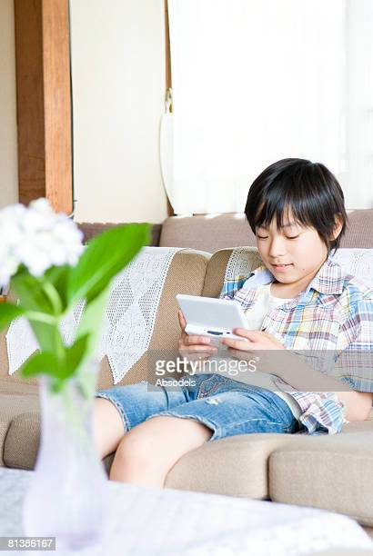 boy sitting on sofa and playing  with handheld video game in living room - handheld video game stock pictures, royalty-free photos & images