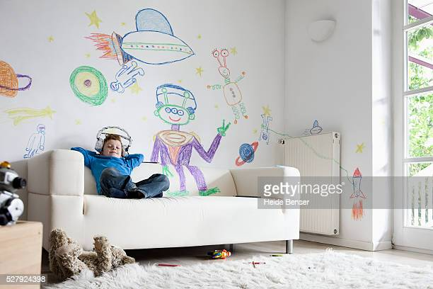Boy (7-9) sitting on sofa