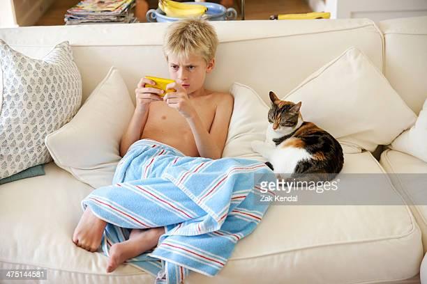 Boy sitting on sofa playing handheld game