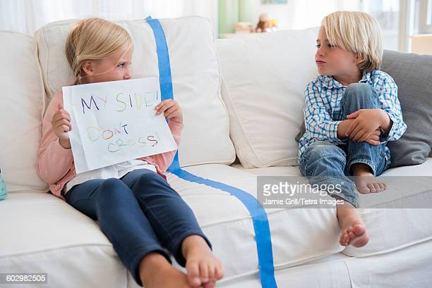 Boy (4-5) sitting on sofa with girl (6-7) holding paper