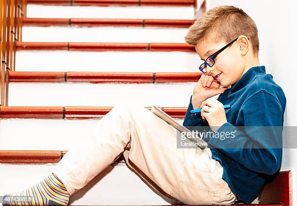 Boy sitting on staircase and drawing on touchpad