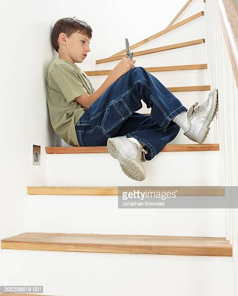 Boy (8-10) sitting on stairs, using mobile phone, side view