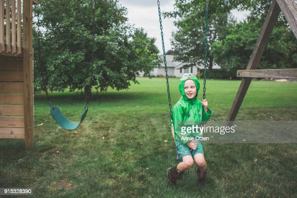 Boy sitting on swing set swing