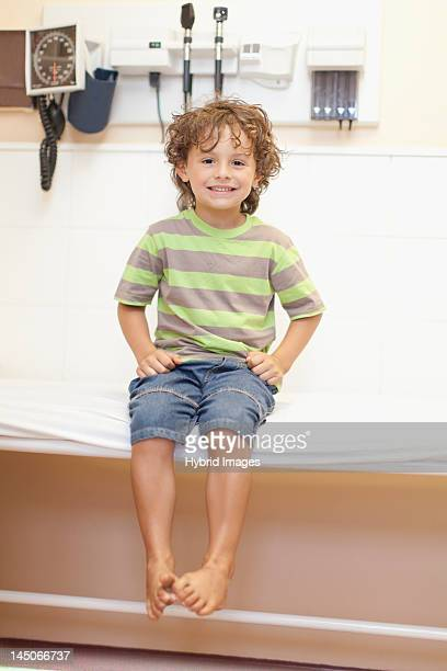 Boy sitting on table in doctors office