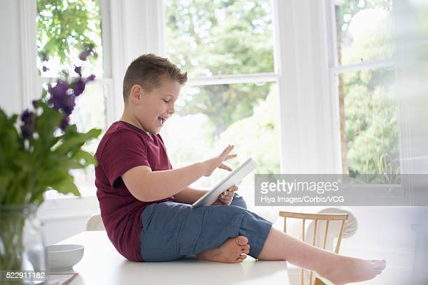 Boy (10-12 years) sitting on table, using digital tablet