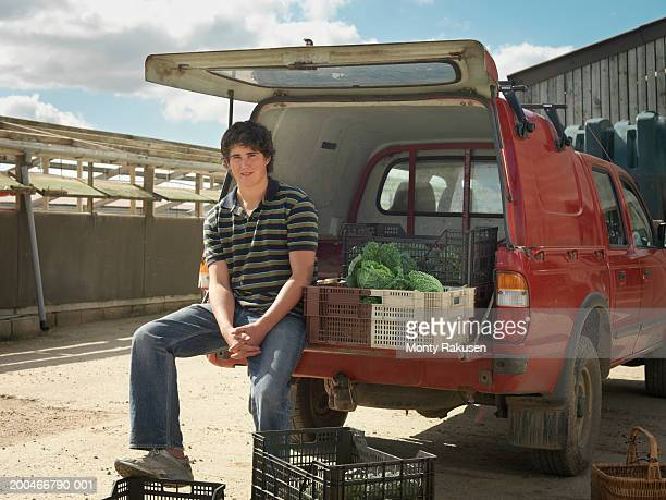 Boy (15-17) sitting on tailgate of delivery van, portrait