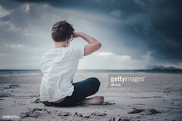 Boy sitting on the beach and looking forward