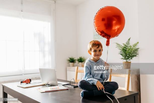 Boy sitting on the dining table with a red balloon in his hand