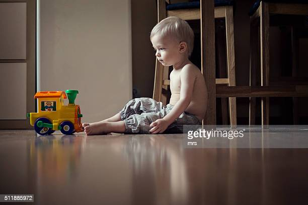 Boy sitting on the floor and staring at the toy train
