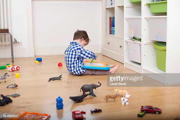 A boy sitting on the floor, drawing on a tablet, surrounded by various toys