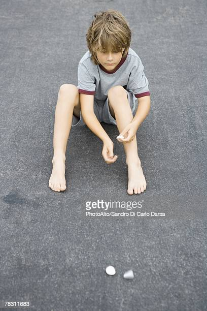 Boy sitting on the ground throwing pebbles, high angle view