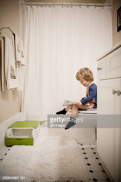 Boy (2-4) sitting on toilet, looking at magazine, side view