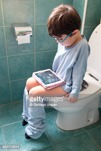 Boy Sitting On Toilet While Looking At Digital Tablet