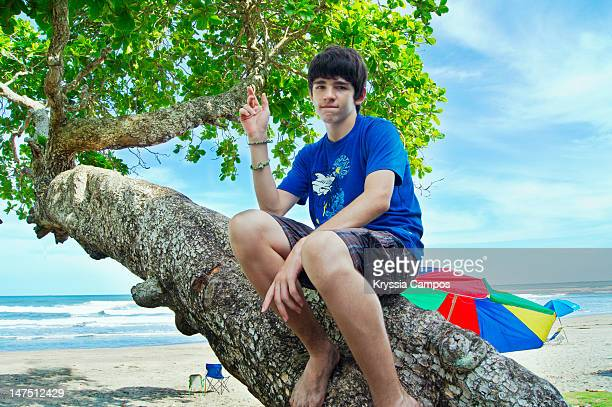 Boy sitting on tree in front of beach