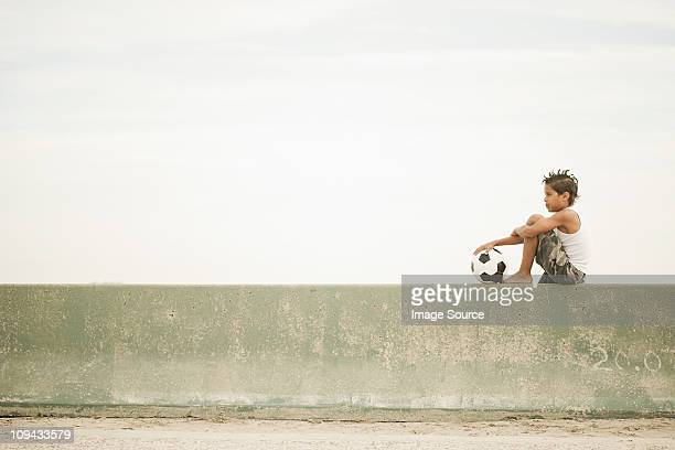 boy sitting on wall with football - stone wall stock pictures, royalty-free photos & images