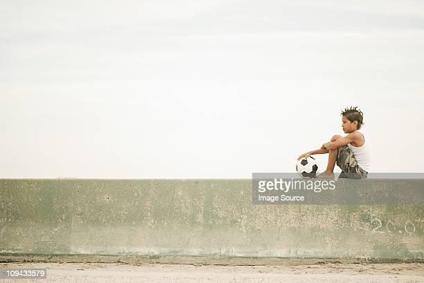 boy sitting on wall with football - stone wall bildbanksfoton och bilder