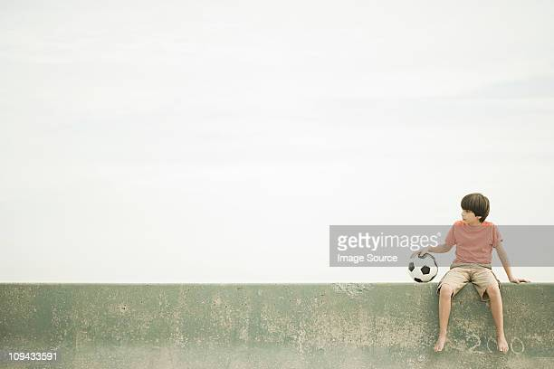 Boy sitting on wall with football