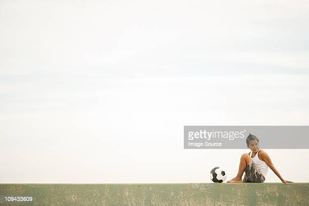 Niño sentado sobre pared con de fútbol