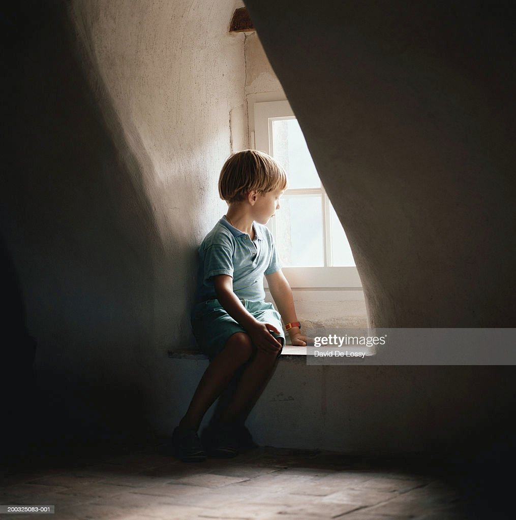 Boy (6-7) sitting on window sill, looking out window : Stock Photo