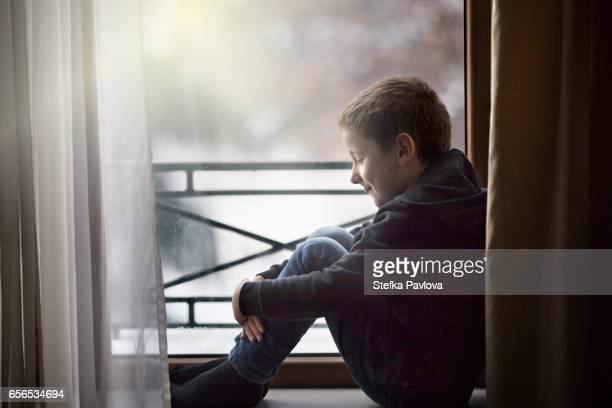 Boy sitting on window sill, looking out window