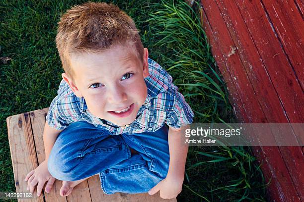 Boy sitting on wooden crate