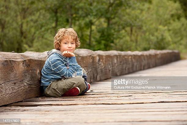 Boy sitting on wooden dock