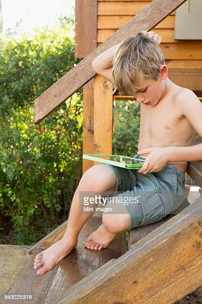 A boy sitting outside, playing on his digital tablet.