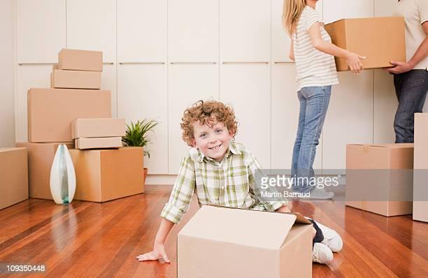 Junge sitzend mit box auf dem Boden seiner neuen Haus