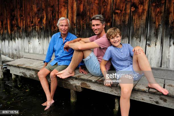 Boy sitting with grandfather and father together on jetty in summer