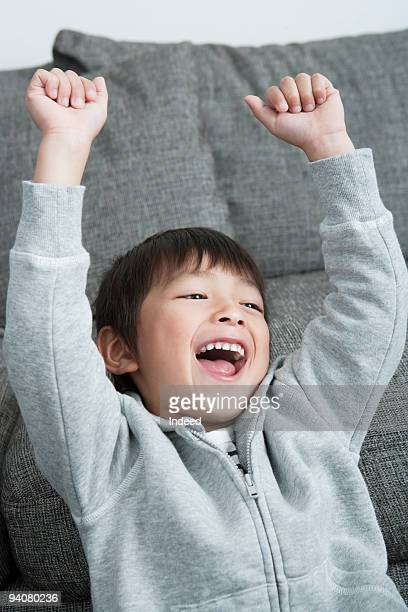 A boy sitting with his arms raised