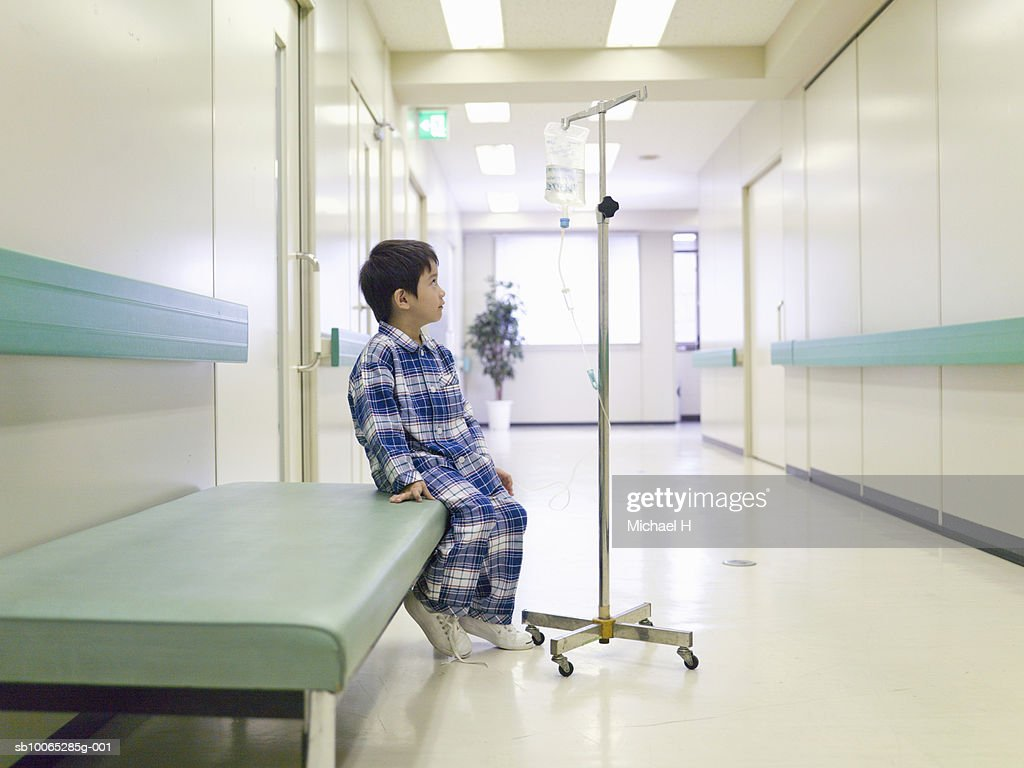 Boy (5-6) sitting with medicine drip in hospital corridor : Foto stock