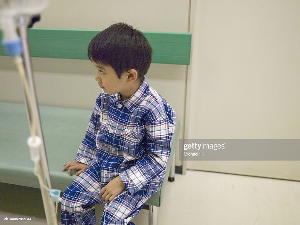 Boy (5-6) sitting with medicine drip in hospital corridor : Foto stock