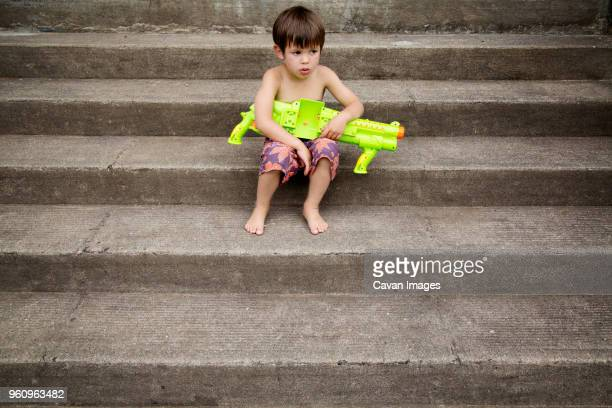 Boy sitting with water gun on stairs