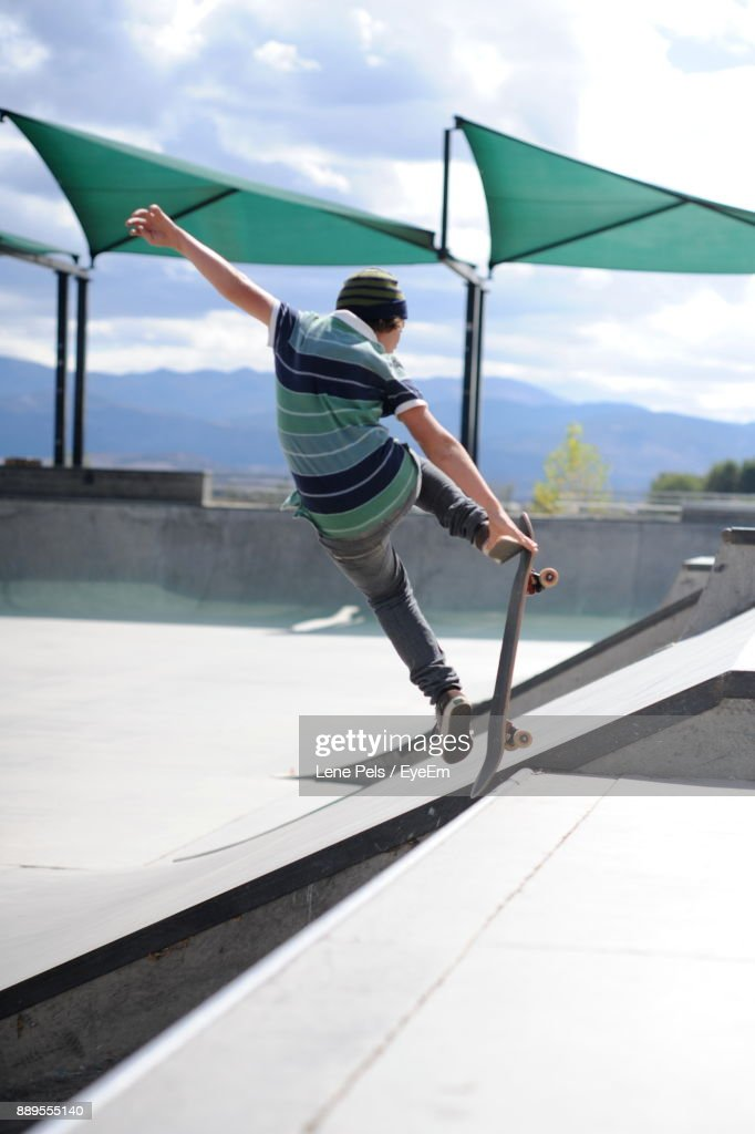 Boy Skateboarding At Park Against Sky : Stock Photo