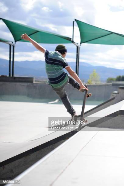 boy skateboarding at park against sky - lene pels imagens e fotografias de stock