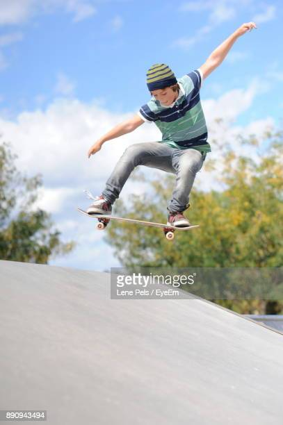 boy skateboarding in mid-air against sky - lene pels stockfoto's en -beelden