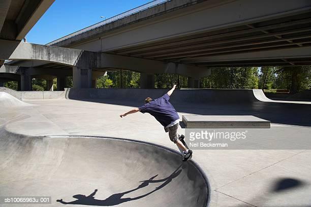 Boy skateboarding in skate park, rear view