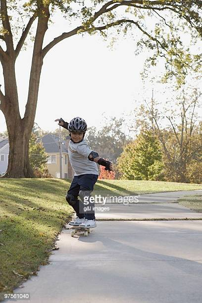 boy skateboarding on sidewalk - padding stock photos and pictures